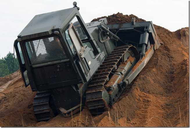 Bulldozer climbing a mound of dirt.